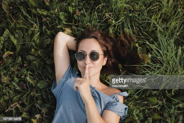 portrait of smiling woman wearing sunglasses lying in grass - versierde jurk stockfoto's en -beelden