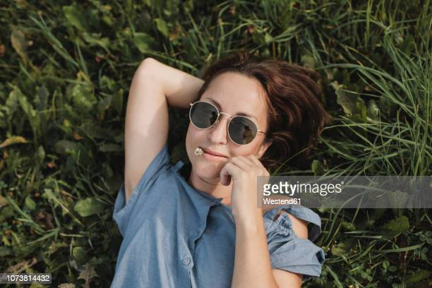 portrait of smiling woman wearing sunglasses lying in grass with flower in her mouth - baumblüte stock-fotos und bilder