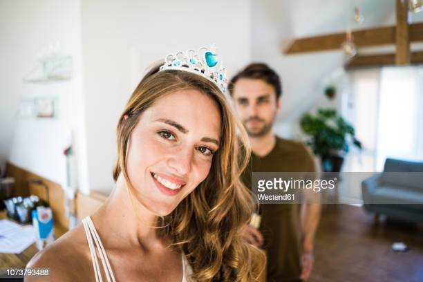 portrait of smiling woman wearing tiara at home with man in background - eitelkeit stock-fotos und bilder