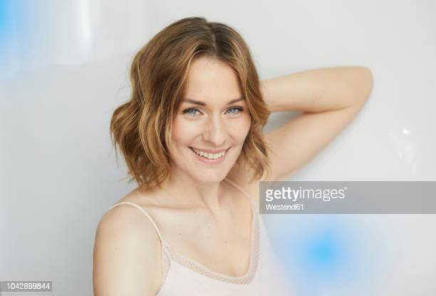 portrait of smiling woman wearing top - dessous stock-fotos und bilder