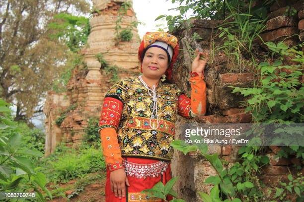portrait of smiling woman wearing traditional clothing standing by old wall - ko ko htike aung stock pictures, royalty-free photos & images