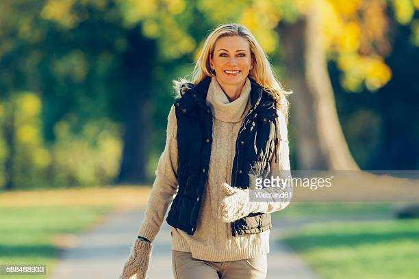 Portrait of smiling woman wearing warm clothes walking in a park