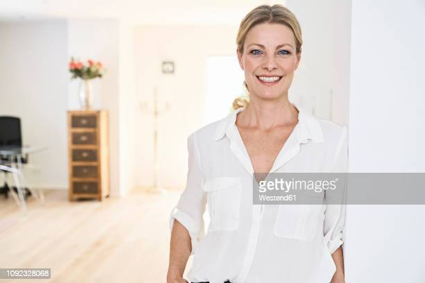 portrait of smiling woman wearing white blouse at home - bluse stock-fotos und bilder
