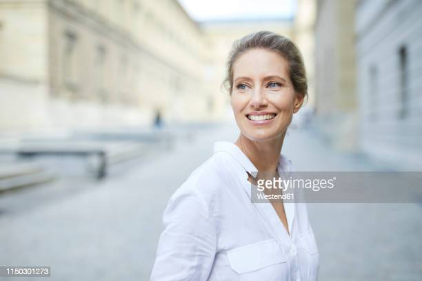 portrait of smiling woman wearing white shirt in the city - 40 44 jahre stock-fotos und bilder