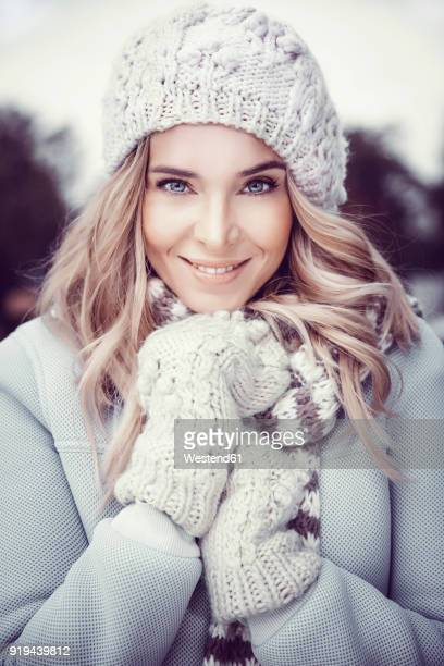 Portrait of smiling woman wearing woolly hat and gloves