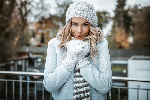 Portrait of smiling woman wearing woolly hat, gloves and scarf - gettyimageskorea