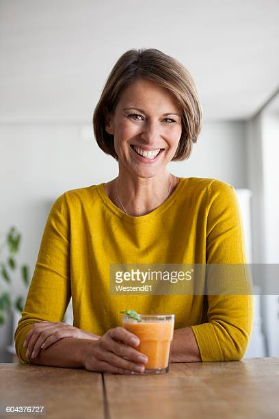 portrait of smiling woman with a smoothie - one mature woman only stock-fotos und bilder