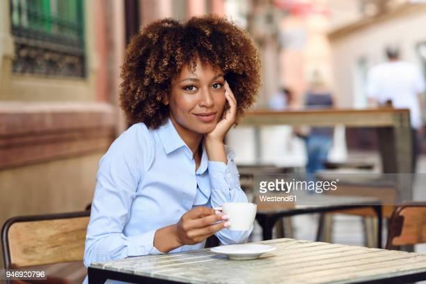 portrait of smiling woman with afro hairstyle sitting in outdoor cafe - pausa para o café - fotografias e filmes do acervo