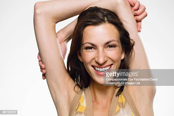 "portrait of smiling woman with arms above her head - ""compassionate eye"" bildbanksfoton och bilder"