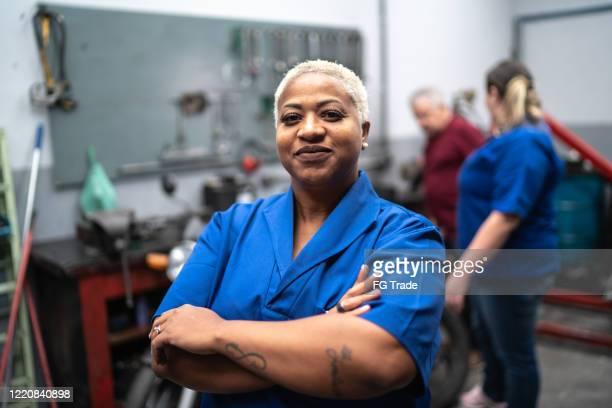 portrait of smiling woman with arms crossed in auto repair - cabelo curto comprimento de cabelo imagens e fotografias de stock