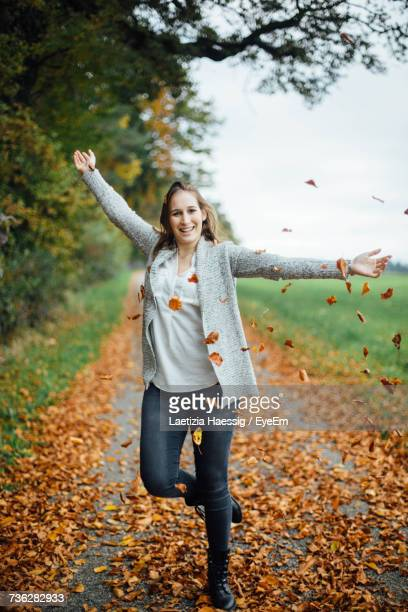 Portrait Of Smiling Woman With Arms Outstretched Standing On Footpath