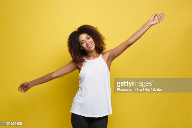portrait of smiling woman with arms outstretched standing on yellow background - arms outstretched stock pictures, royalty-free photos & images