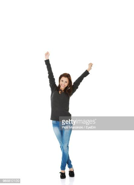 portrait of smiling woman with arms raised standing against white background - braccia alzate foto e immagini stock