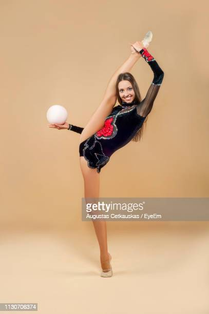 portrait of smiling woman with ball dancing against colored background - lituania fotografías e imágenes de stock