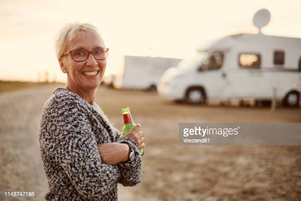 portrait of smiling woman with beer bottle on camping ground in the evening - 雰囲気 ストックフォトと画像