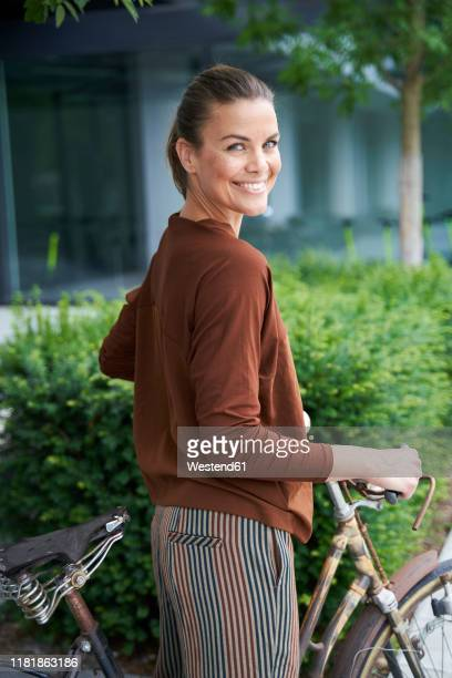 portrait of smiling woman with bicycle in the city - one mature woman only stock pictures, royalty-free photos & images