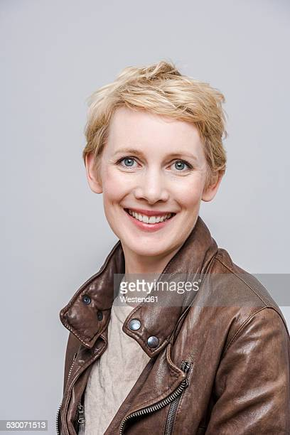 portrait of smiling woman with blond short hair - one mid adult woman only stock pictures, royalty-free photos & images