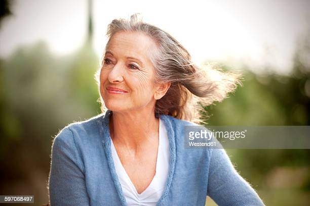 Portrait of smiling woman with blowing hair in the garden