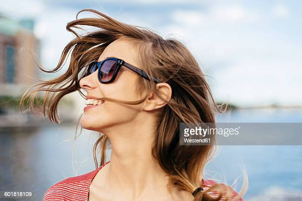 Portrait of smiling woman with blowing hair wearing sunglasses