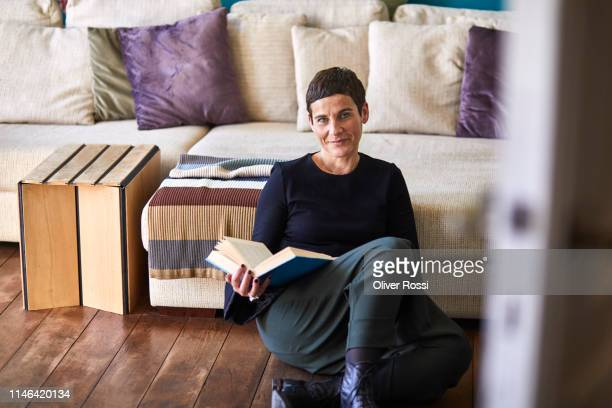 portrait of smiling woman with book sitting on the floor at home - kurzes haar stock-fotos und bilder