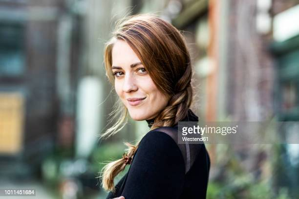portrait of smiling woman with braid - turning stock pictures, royalty-free photos & images