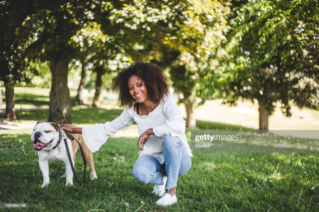 Portrait of smiling woman with bulldog on grassy field at park : Stock Photo
