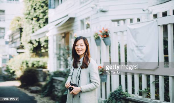 portrait of smiling woman with camera exploring in city street - セレクティブフォーカス ストックフォトと画像