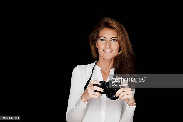 portrait of smiling woman with camera in front of black background - high contrast stock pictures, royalty-free photos & images