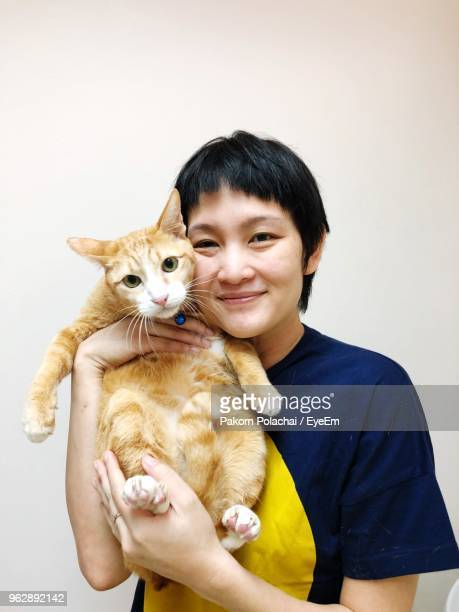 Portrait Of Smiling Woman With Cat Against Wall