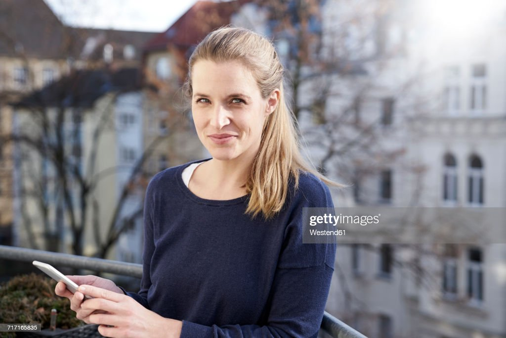 Portrait of smiling woman with cell phone on balcony : Stock-Foto