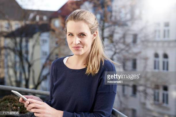 portrait of smiling woman with cell phone on balcony - 35 39 jahre stock-fotos und bilder