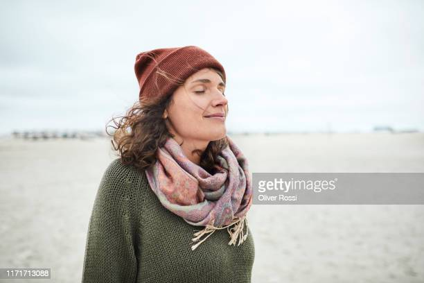 portrait of smiling woman with closed eyes on the beach - headwear stock pictures, royalty-free photos & images