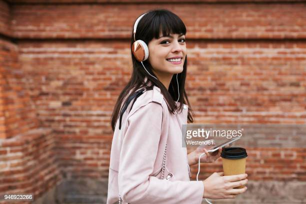 portrait of smiling woman with coffee, cell phone and headphones at brick wall - la vingtaine photos et images de collection