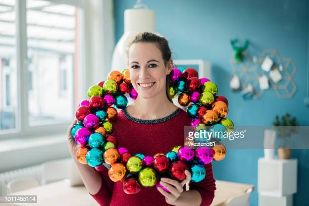 portrait of smiling woman with colourful christmas bauble wreath - adviento fotografías e imágenes de stock