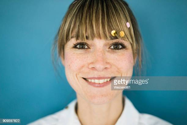 portrait of smiling woman with confetti in her hair - braune augen stock-fotos und bilder