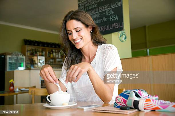 portrait of smiling woman with cup of cappucino in a cafe - sugar coffee stock photos and pictures