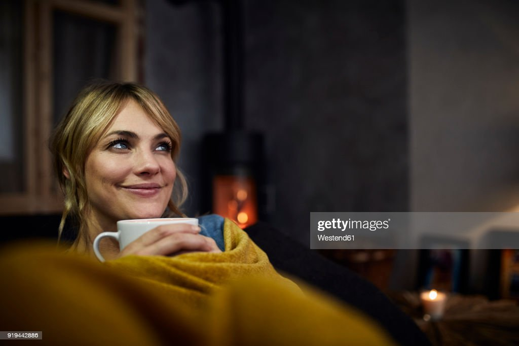 Portrait of smiling woman with cup of coffee relaxing on couch at home in the evening : Stock-Foto