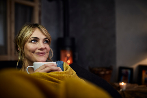 Portrait of smiling woman with cup of coffee relaxing on couch at home in the evening - gettyimageskorea