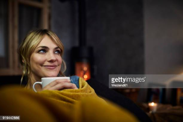 portrait of smiling woman with cup of coffee relaxing on couch at home in the evening - calientes fotografías e imágenes de stock
