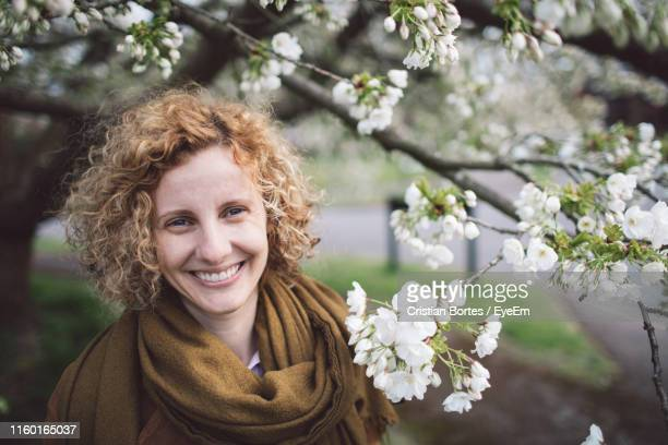 portrait of smiling woman with curly hair by flowering tree - bortes stock photos and pictures