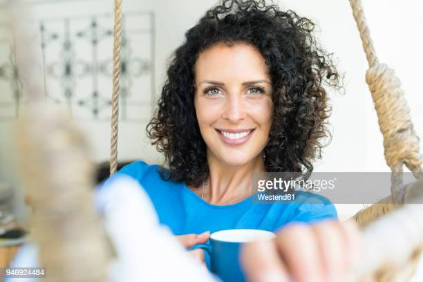 portrait of smiling woman with curly hair holding cup of coffee - une seule femme d'âge moyen photos et images de collection