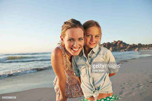 Portrait of smiling woman with daughter (10-12) on beach