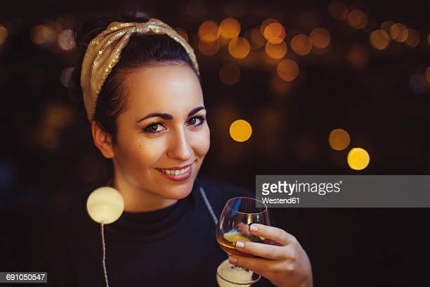 Portrait of smiling woman with drink wearing golden hair-band