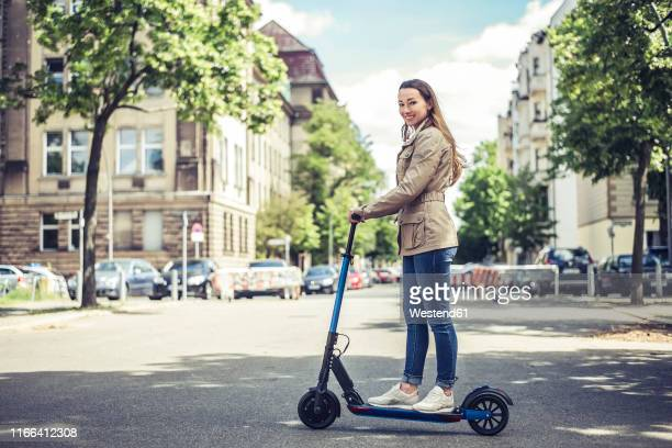 portrait of smiling woman with e-scooter in the city - strom haare stock-fotos und bilder