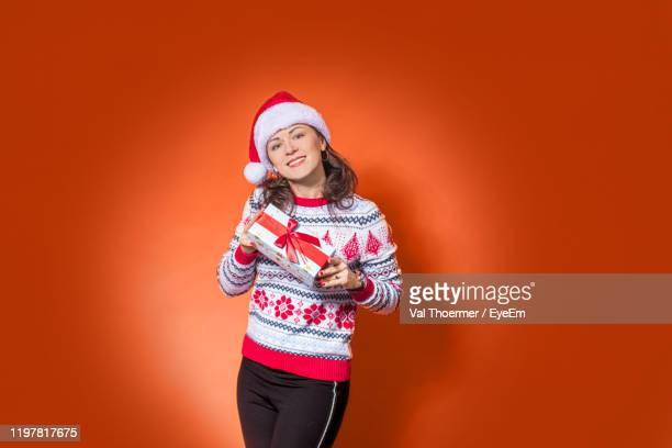 portrait of smiling woman with gift standing against red background - val thoermer stock-fotos und bilder