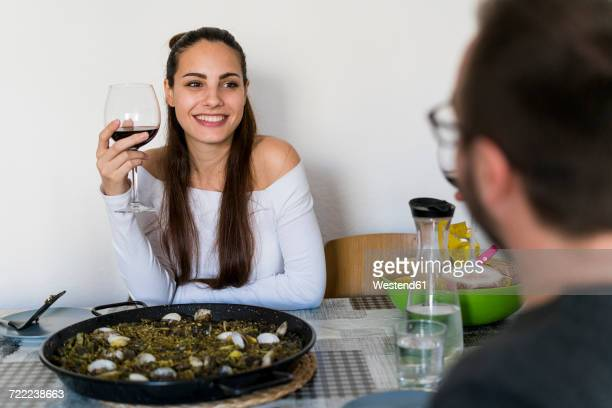 portrait of smiling woman with glass of red wine sitting at laid table looking at her boyfriend - southern european descent stock pictures, royalty-free photos & images