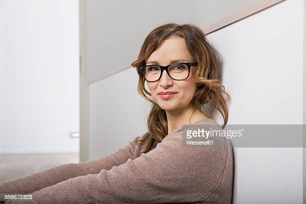 Portrait of smiling woman with glasses leaning against wall