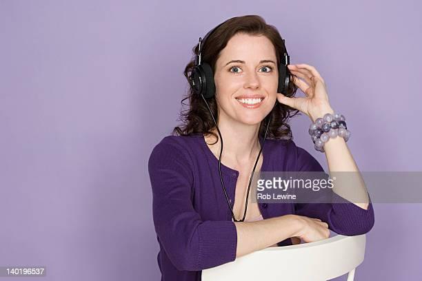 Portrait of smiling woman with headphones on purple background, studio shot