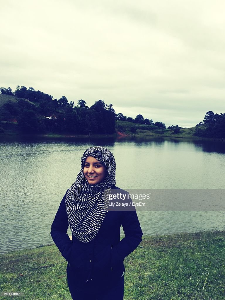 Portrait Of Smiling Woman With Hijab Standing By Lake Against Cloudy Sky : Stock Photo