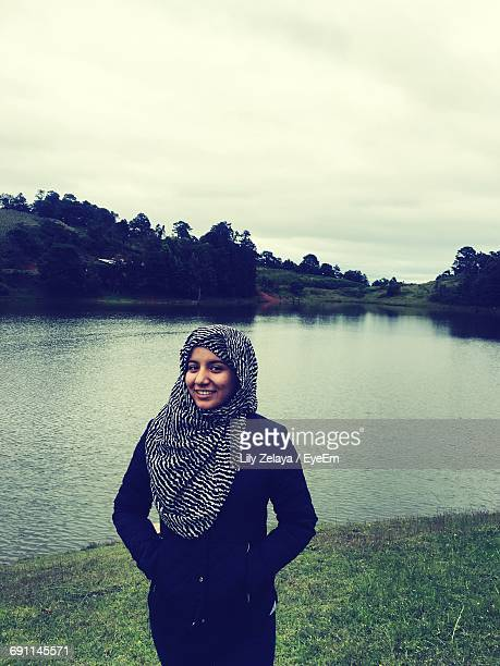 Portrait Of Smiling Woman With Hijab Standing By Lake Against Cloudy Sky